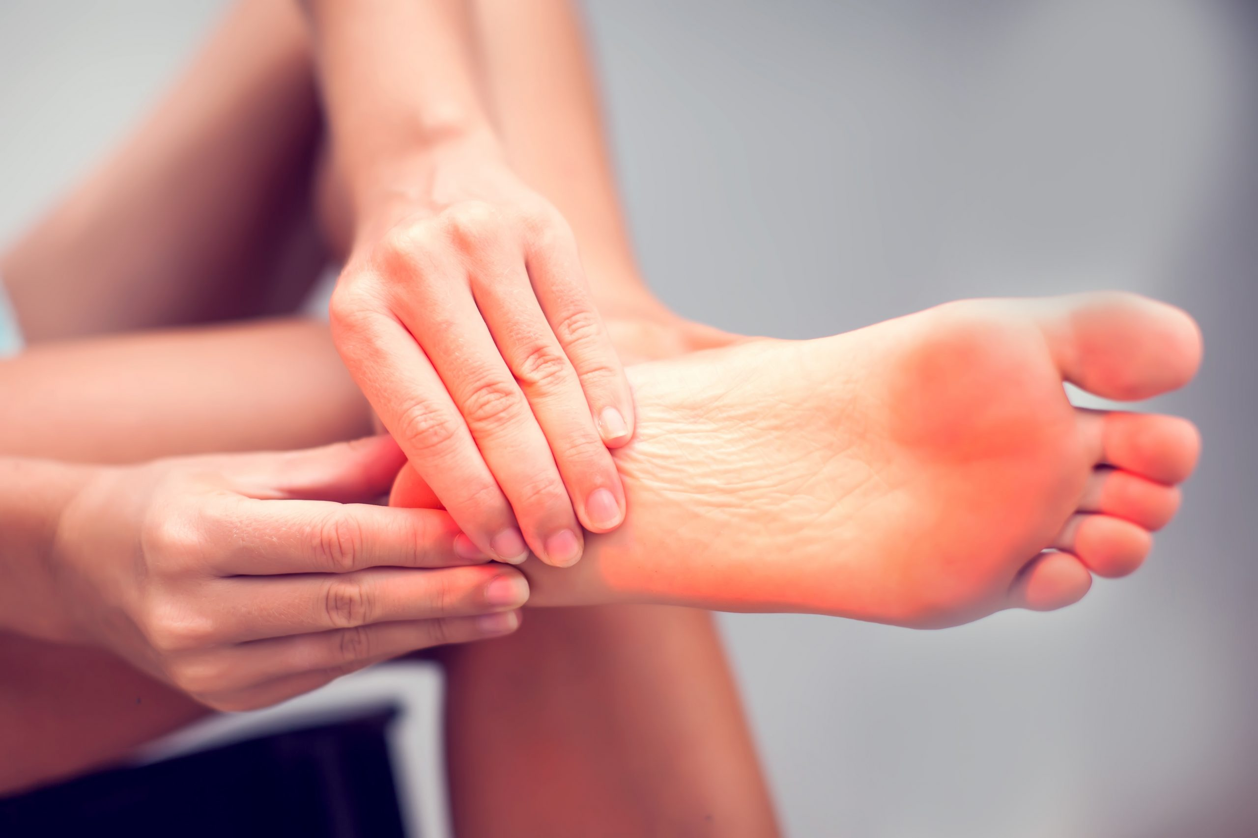person touching their heel in pain